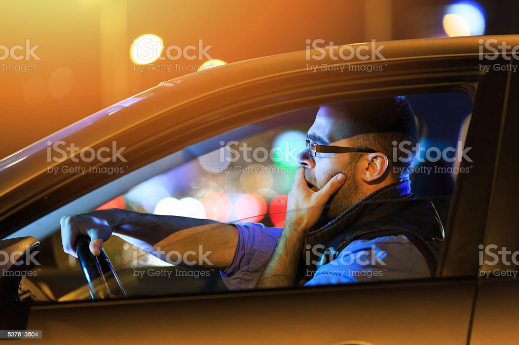 Man sitting in car and yawning by night stock photo