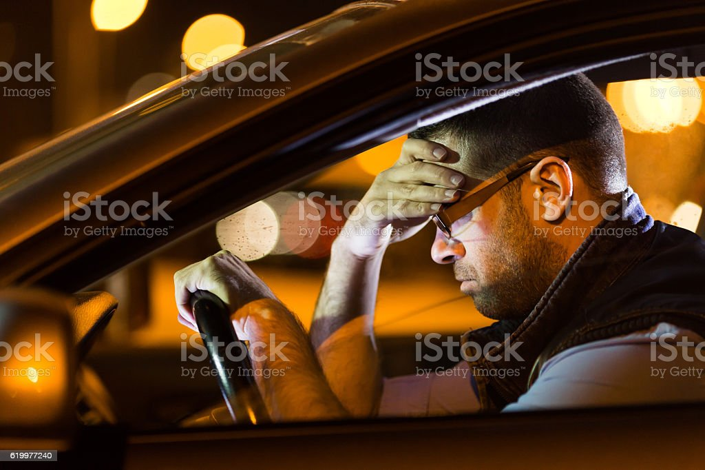 Man sitting in car hand on head stock photo