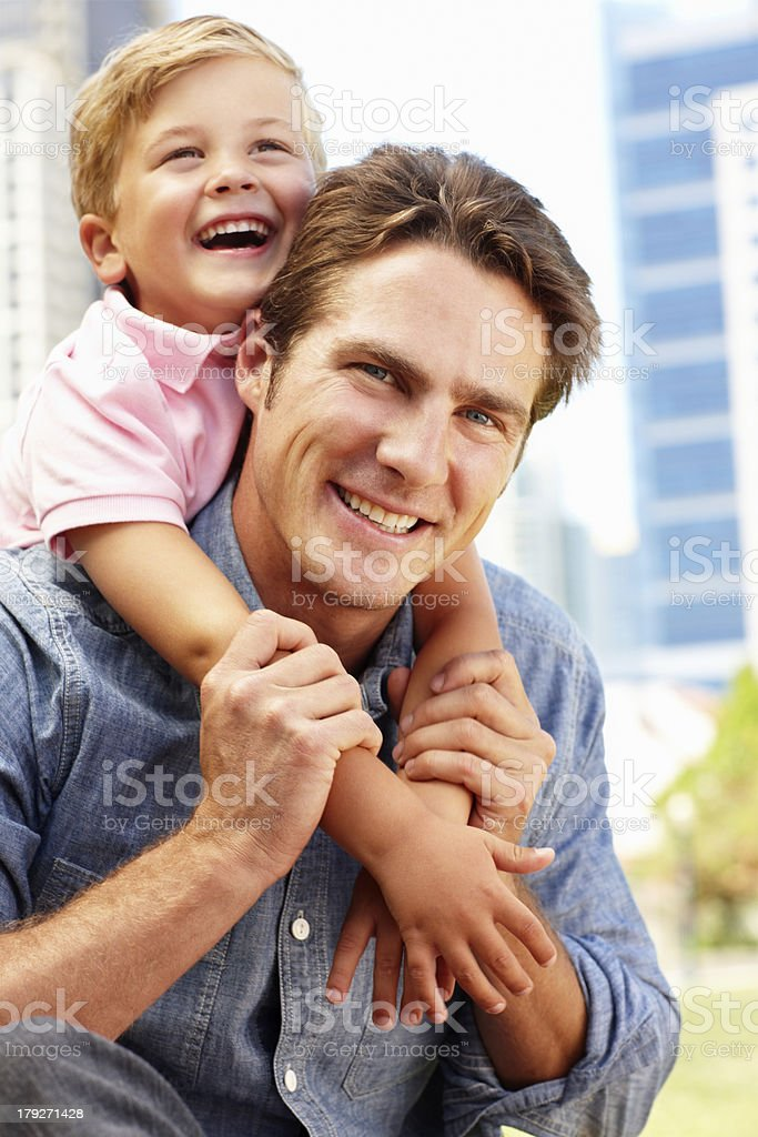 Man sitting in city park with young son royalty-free stock photo