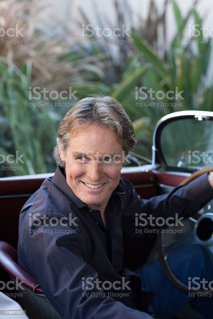 Man sitting in convertible car smiling over his shoulder stock photo