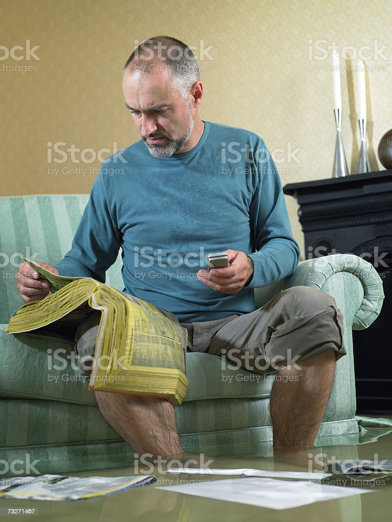 Man sitting in flooded living room using phone stock photo
