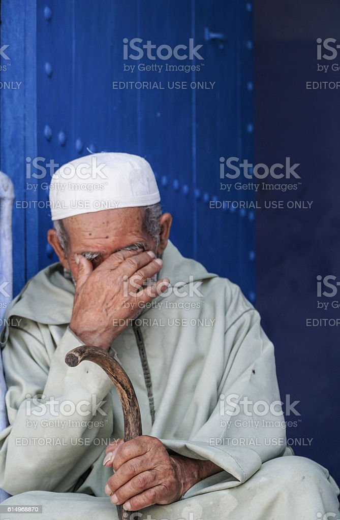 man sitting in front of a blue door in Morocco. stock photo