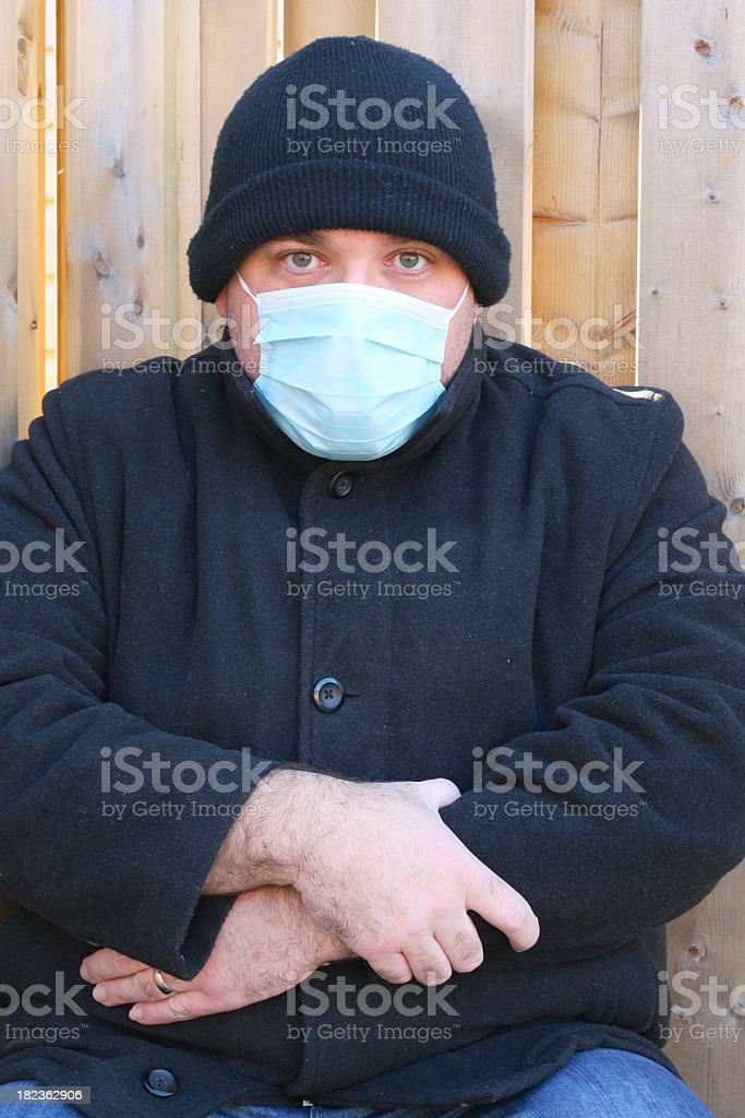 A man sitting in front of a wall wearing a mask stock photo