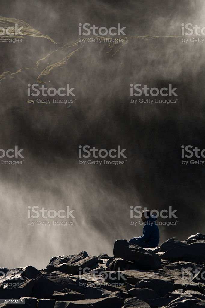Man sitting in front of waterfall stock photo
