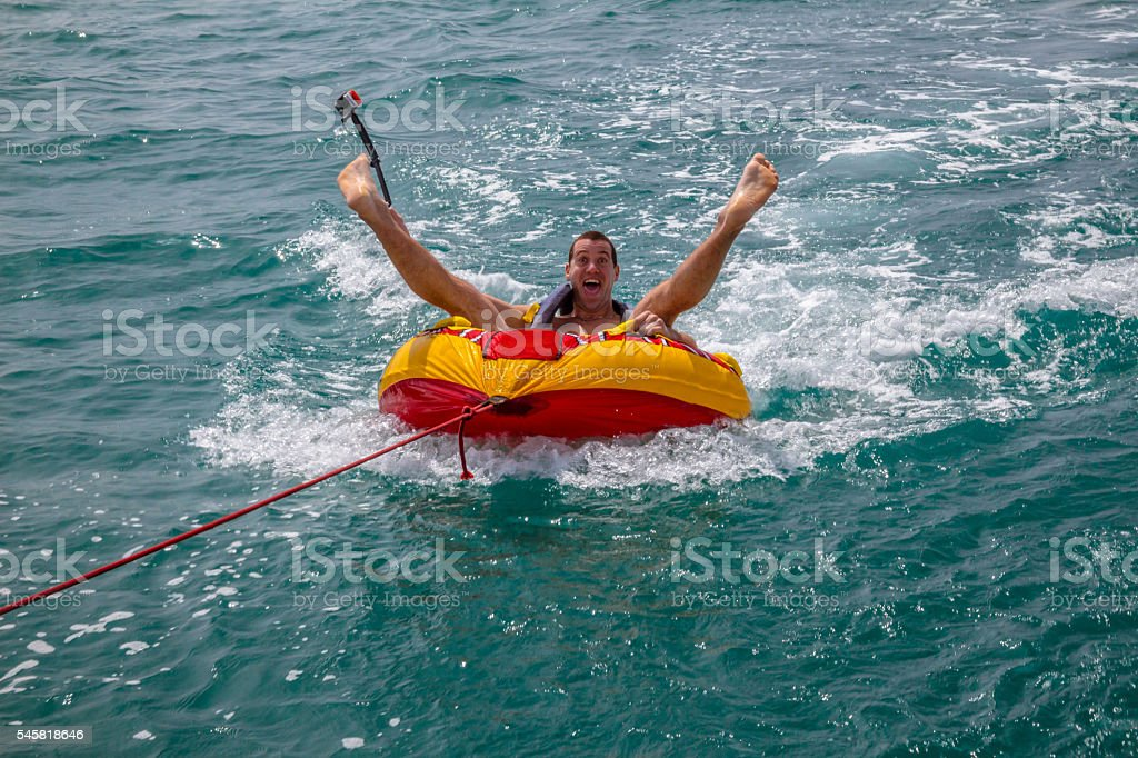 Man sitting in inflatable ring in the water stock photo