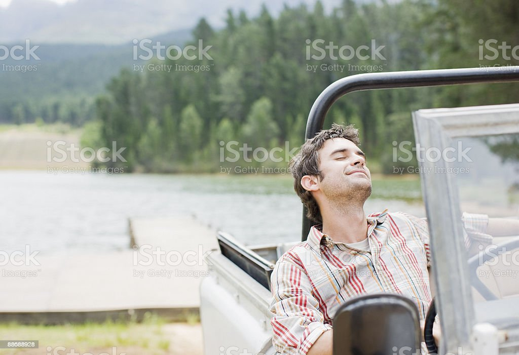 Man sitting in jeep near lake royalty-free stock photo