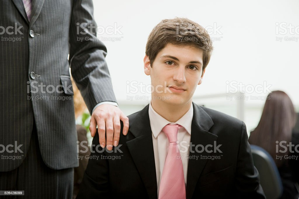 Man sitting in Office With Boss Behind Him stock photo