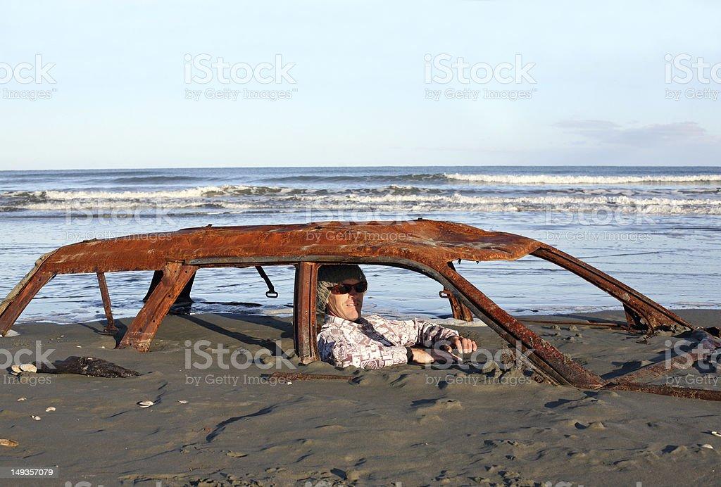 Man sitting in rusty car buried on a beach. stock photo