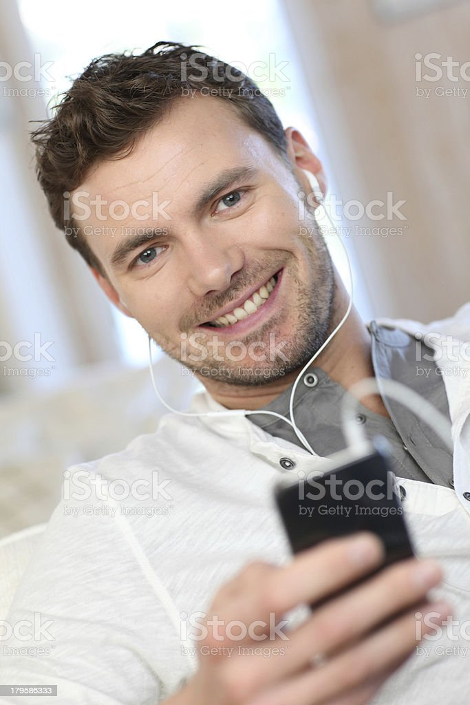 Man sitting in sofa and listening music on smartphone royalty-free stock photo