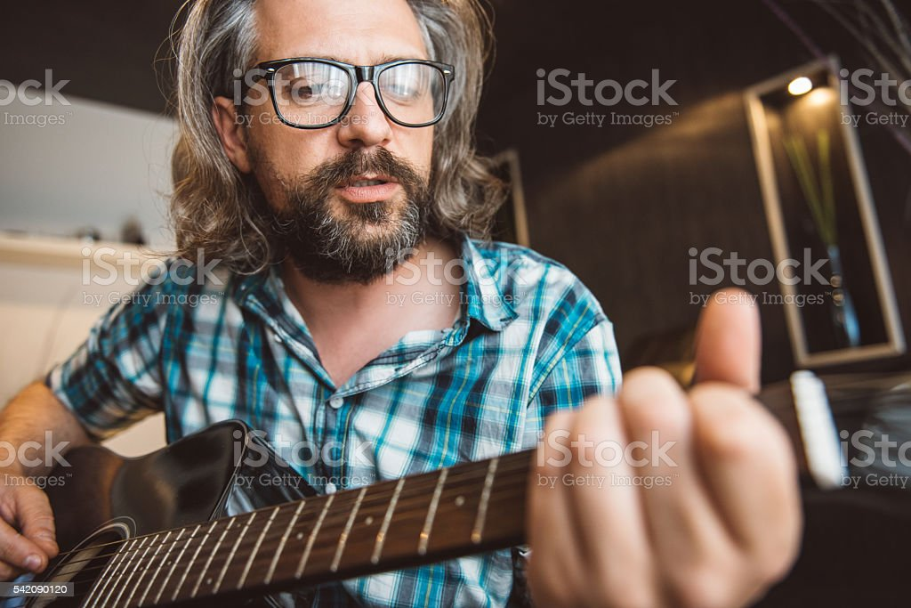 Man sitting in sofa and playing guitar at home stock photo