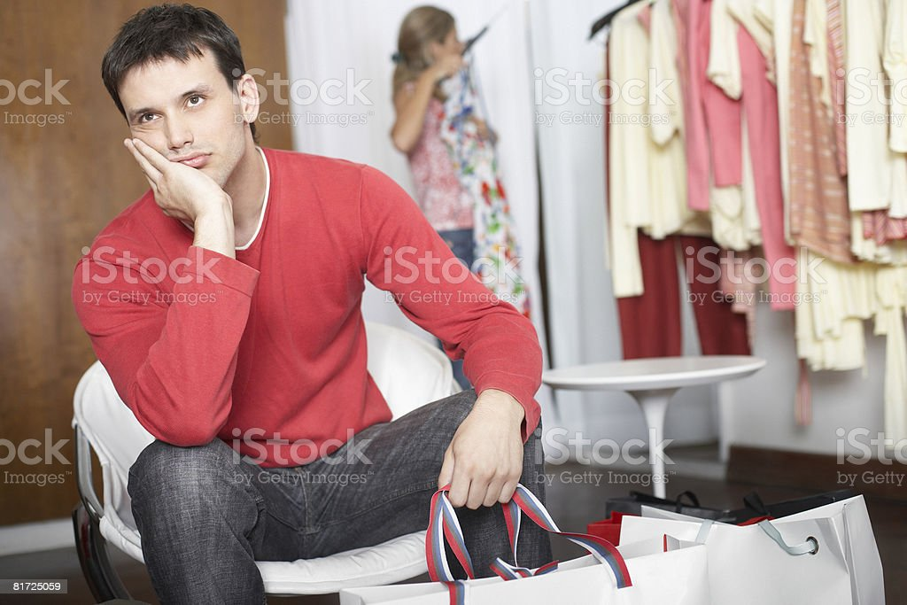 Man sitting in store waiting and looking bored stock photo