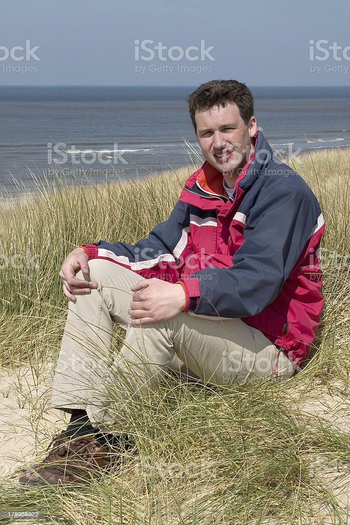 Man sitting in the dunes stock photo