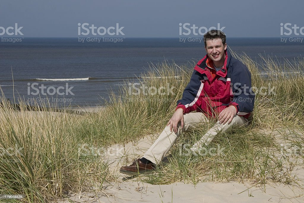 Man sitting in the dunes (Netherlands) stock photo
