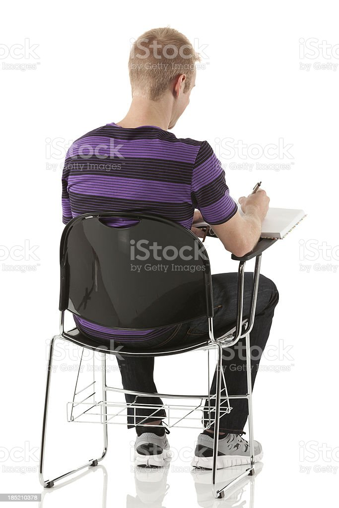Man sitting in writing chair and studying royalty-free stock photo