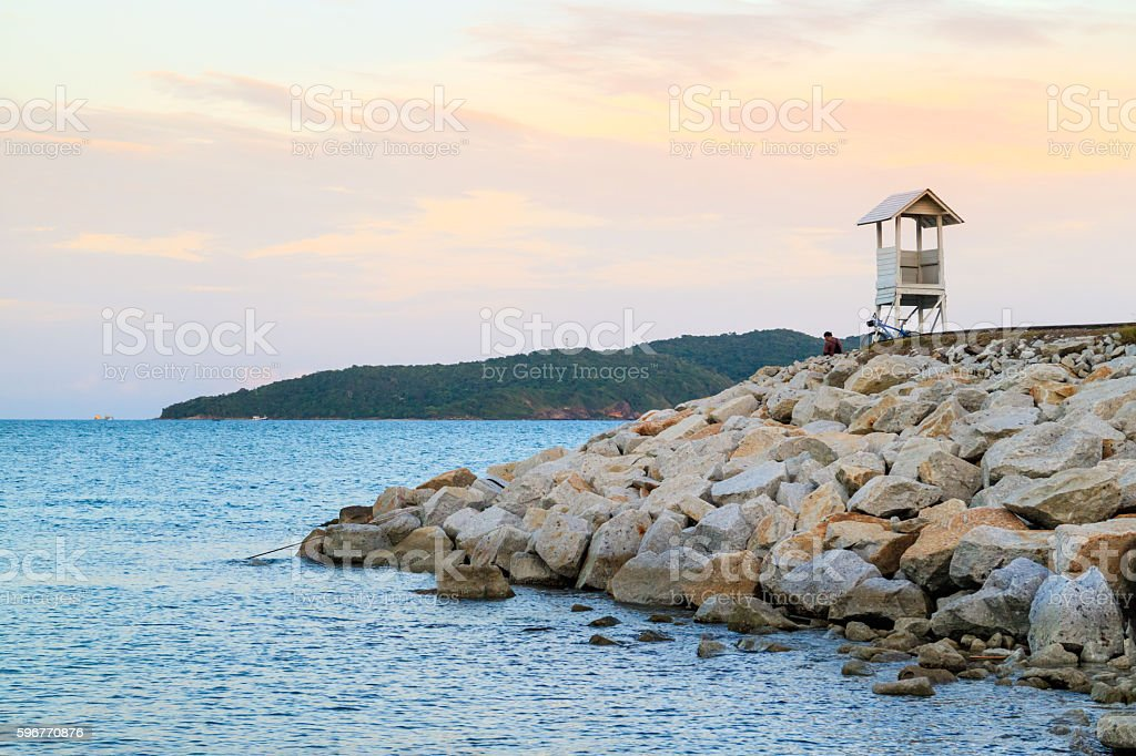 Man sitting near life guard house look at sunset sky. stock photo