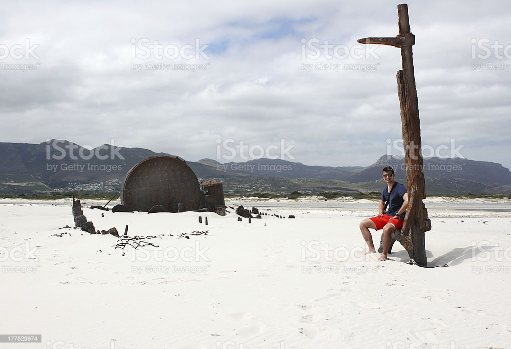 Man sitting near Shipwreck Kakapo at the beach of kommetjie royalty-free stock photo