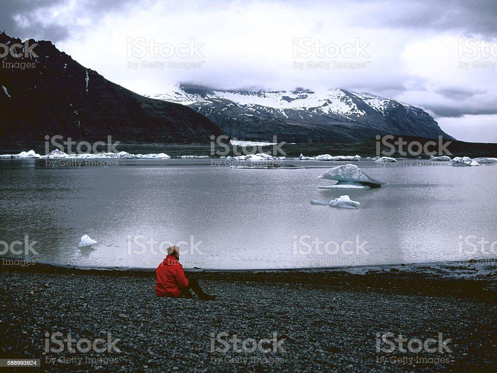 Man sitting near the glacier lagoon stock photo