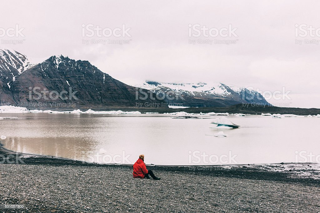 Man sitting near the lake stock photo