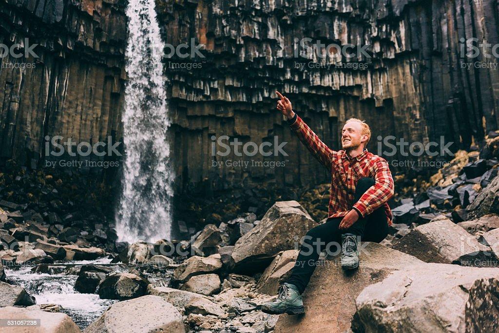 Man sitting near the waterfall stock photo