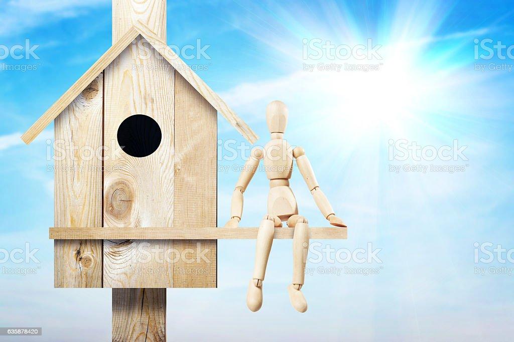 Man sitting next to wooden birdhouse stock photo