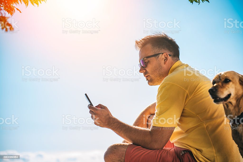 Man sitting on a beach and using smart phone stock photo