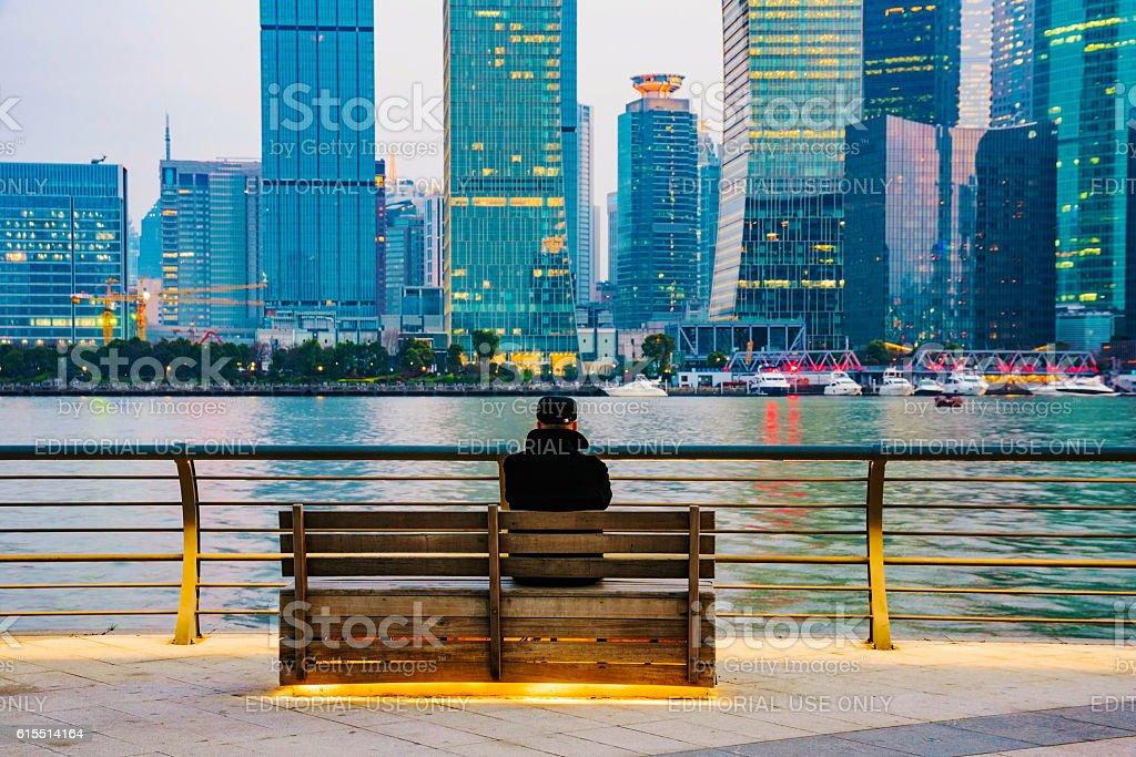 man sitting on a bench on the bund stock photo