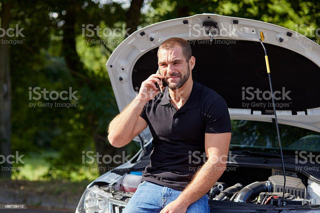 Man sitting on a broken car stock photo