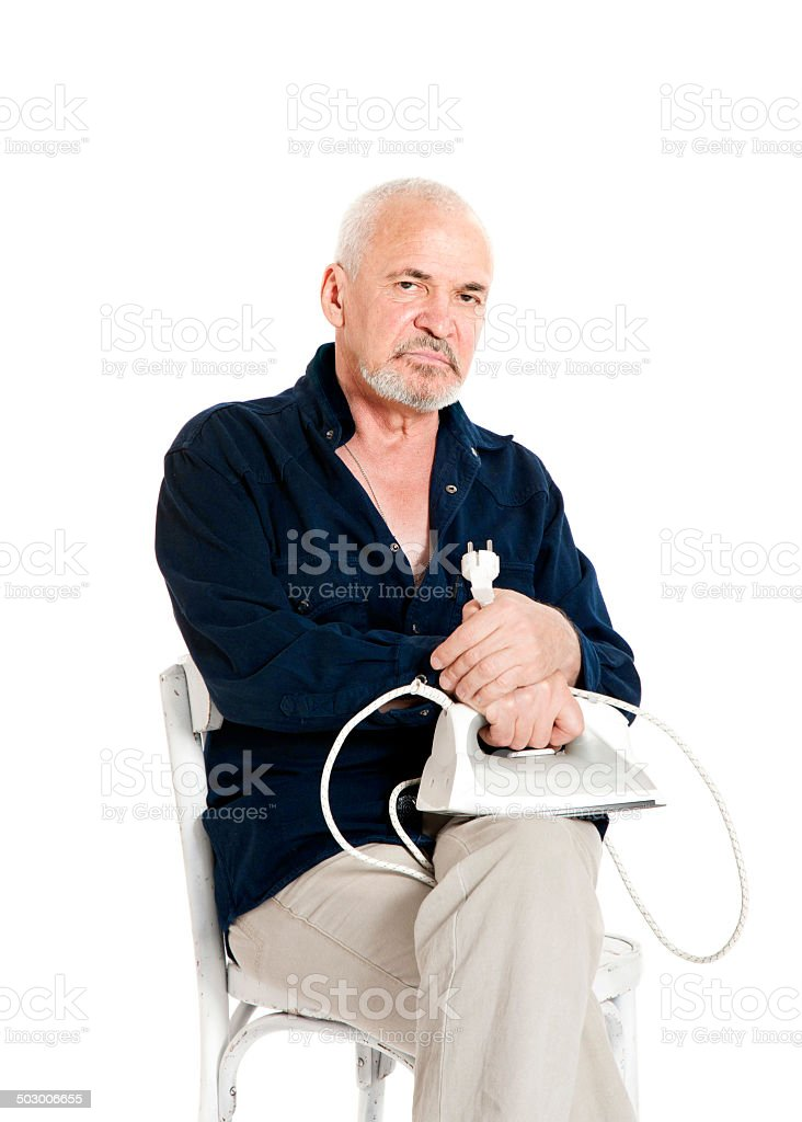 Man sitting on a chair and holding electric iron stock photo