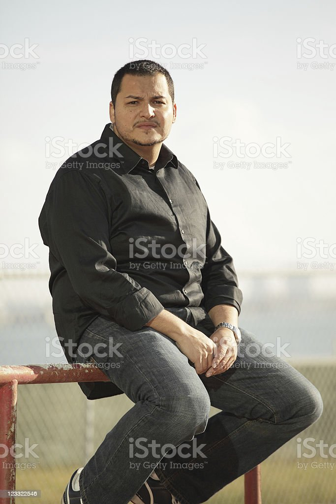 Man sitting on a fence stock photo