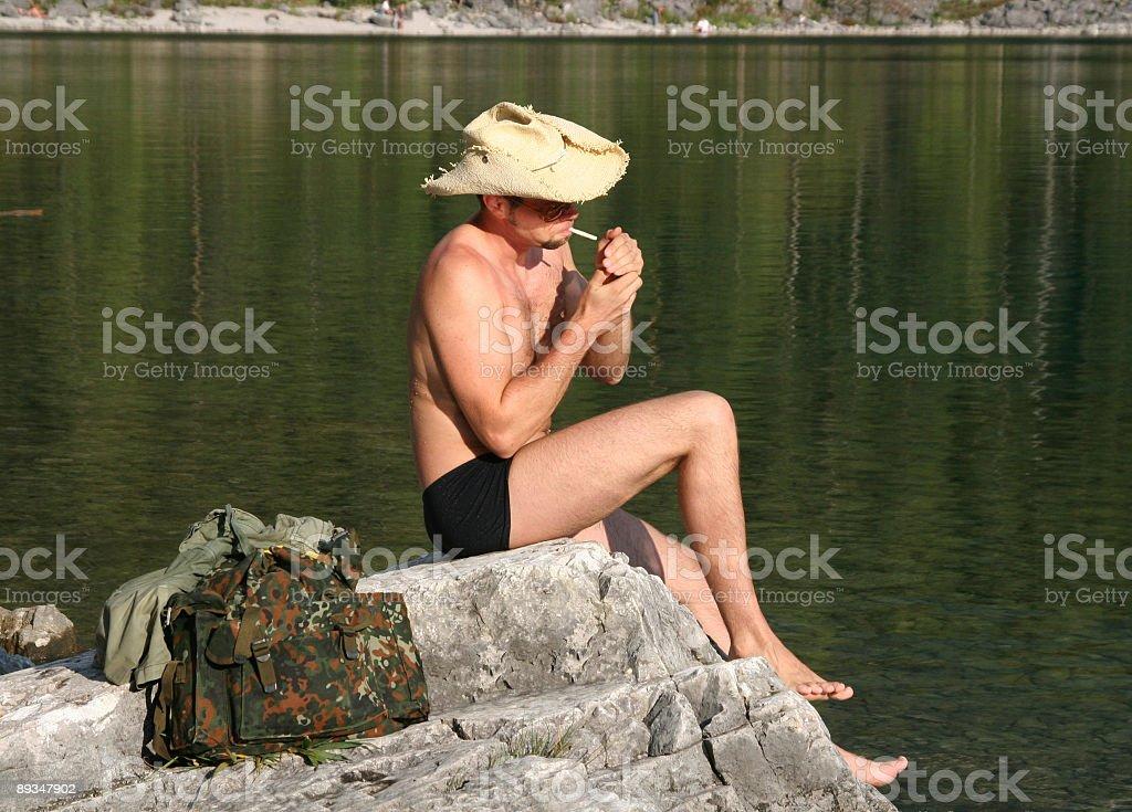 Man sitting on a lake smoking his cigarette stock photo