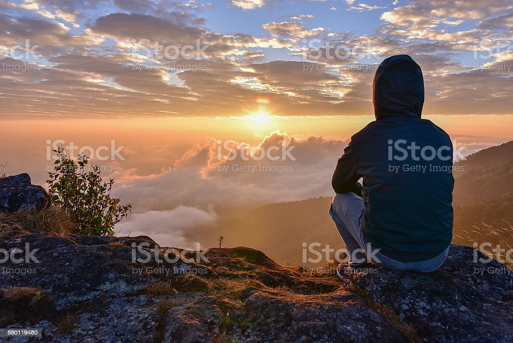 Man sitting on a mountain for watching Sunrise views. stock photo