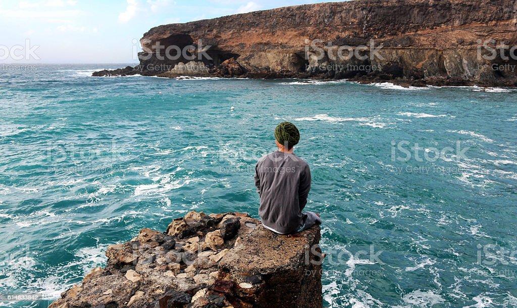 Man sitting on a rock above Atlantic ocean in Fuerteventura stock photo