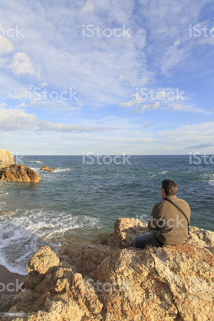 Man sitting on a rock in the beach looking landscape royalty-free stock photo
