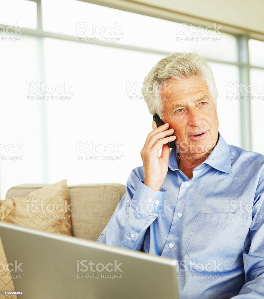 Man sitting on a sofa talking on a cellphone royalty-free stock photo