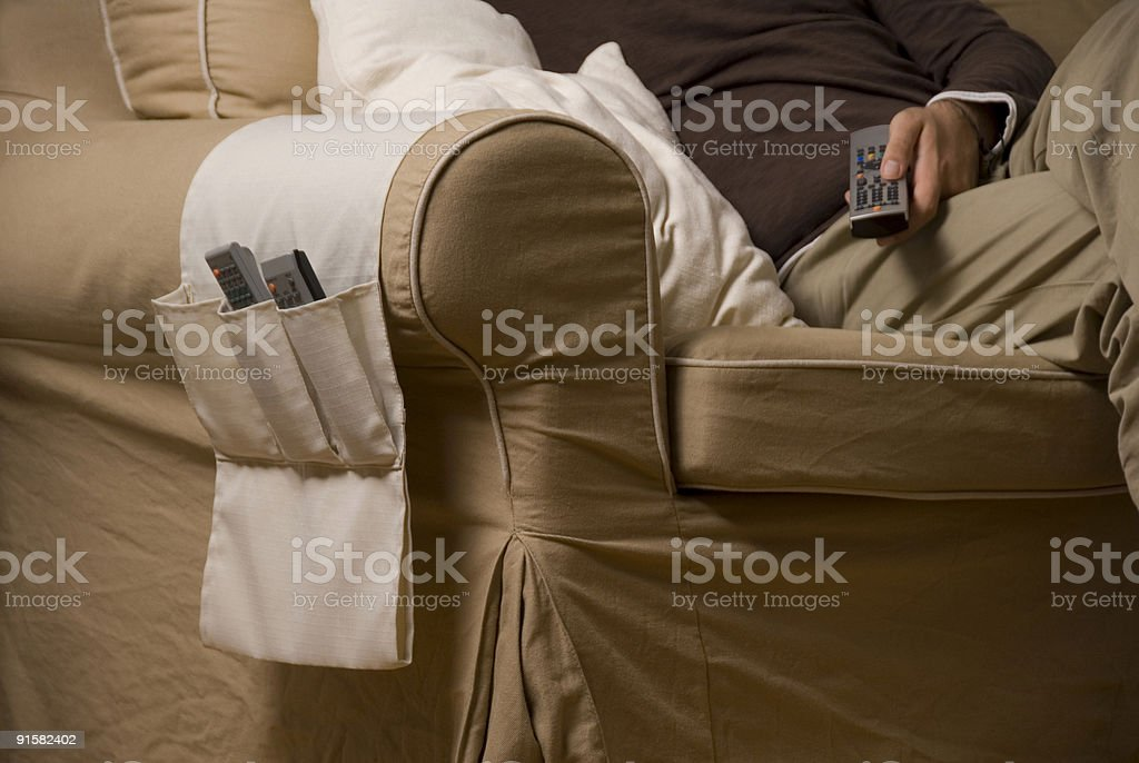 Man sitting on a sofa with remote control royalty-free stock photo