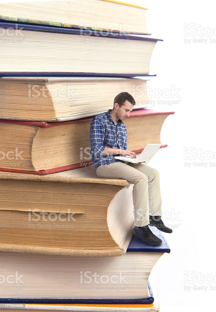 Man sitting on a stack of books and using laptop stock photo