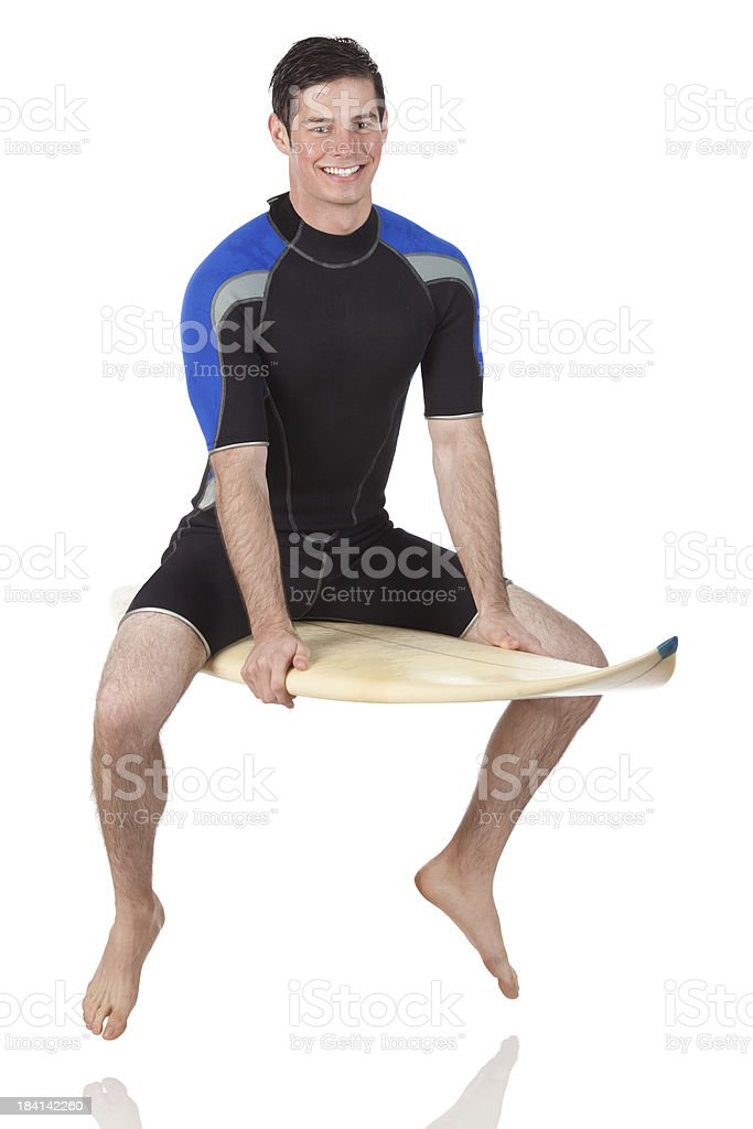 Man sitting on a surfboard stock photo
