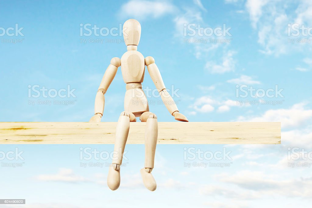 Man sitting on a wooden board over the precipice stock photo