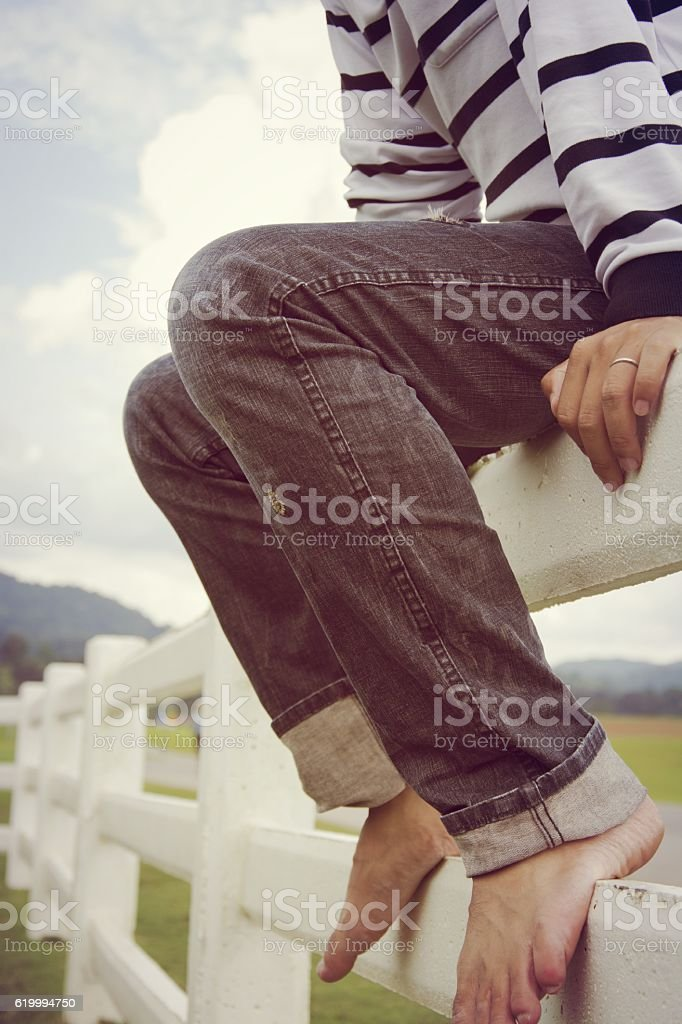 Man sitting on a wooden fence and enjoy for relax royalty-free stock photo