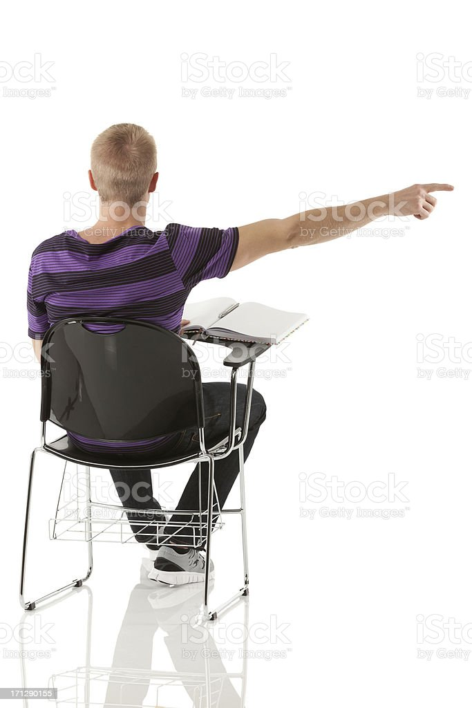 Man sitting on a writing chair and pointing stock photo