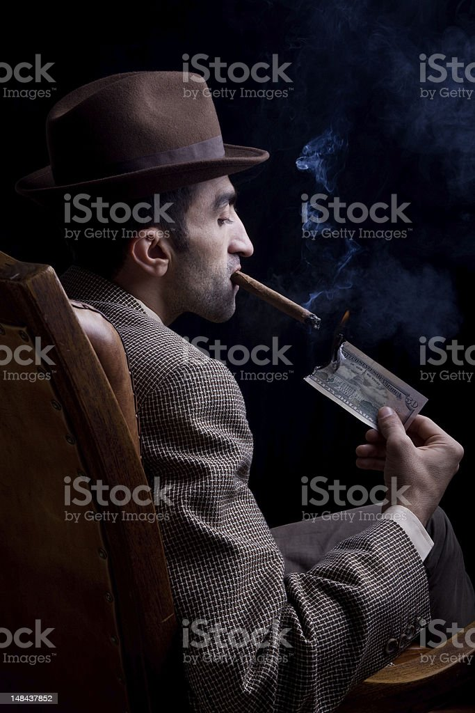 Man sitting on armchair smoking cigar with burning dollar bill royalty-free stock photo