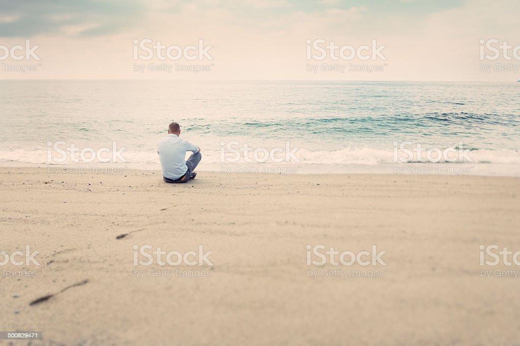Man sitting on beach stock photo