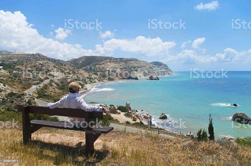 man sitting on bench looking at sea stock photo
