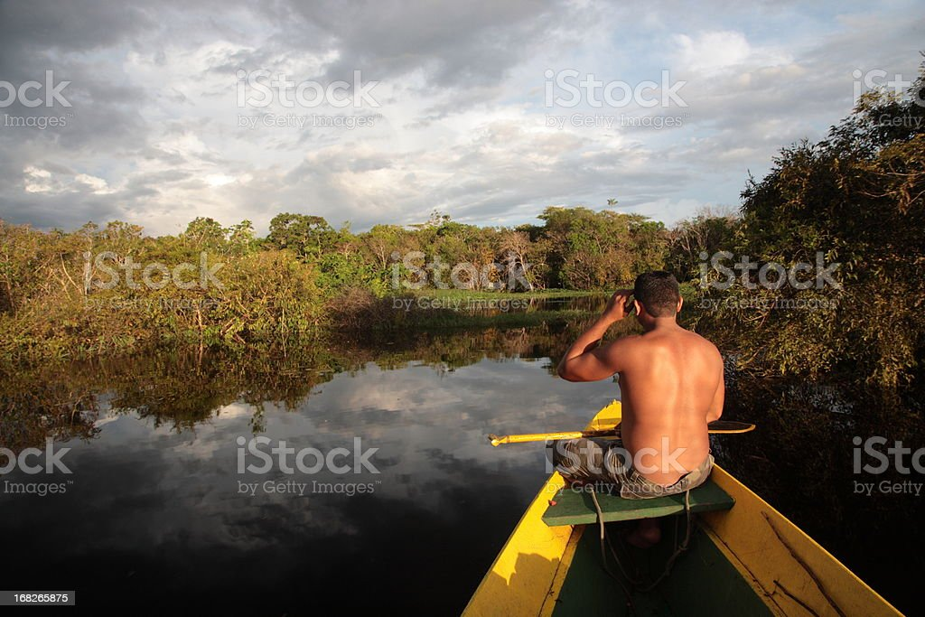 man sitting on boat in Amazon jungle river, Brazil stock photo