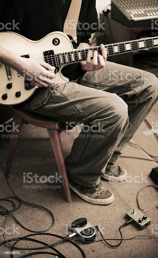 Man Sitting on Chair and Playing Electric Guitar