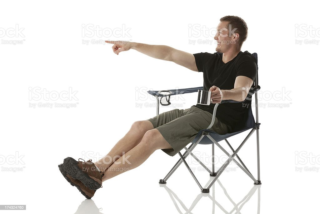 Man sitting on chair with a coffee cup pointing away royalty-free stock photo