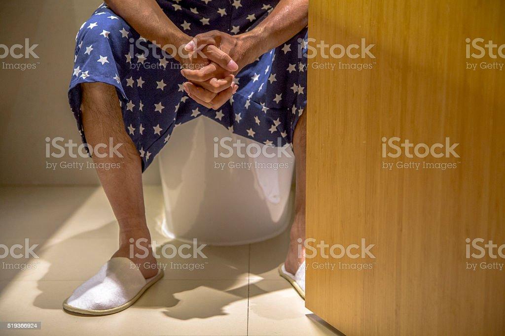 man sitting on closestool stock photo