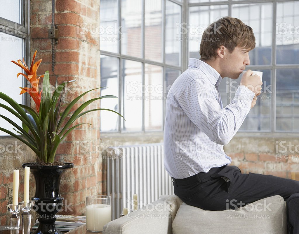 Man sitting on couch back drinking coffee in modern home stock photo