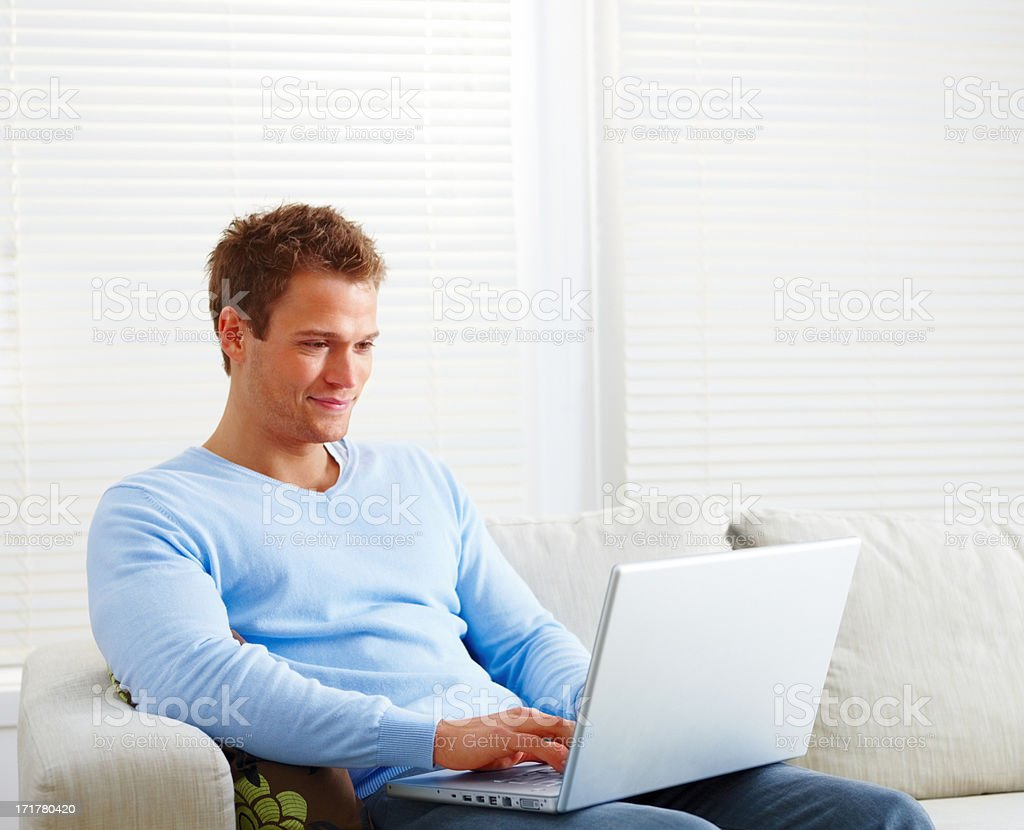 Man sitting on couch using laptop computer stock photo