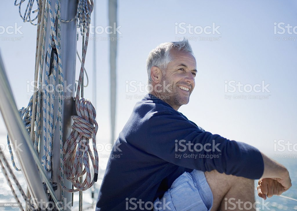 Man sitting on deck of boat stock photo